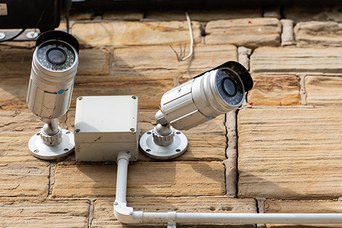 Two outdoor security cameras mounted to a brick wall